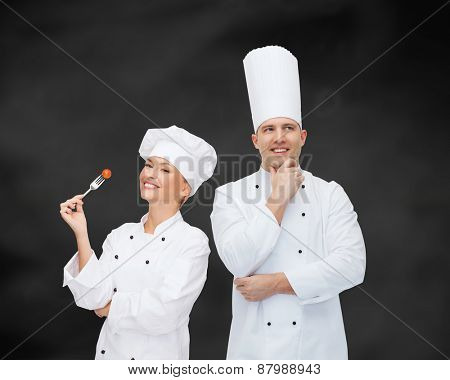 cooking, profession, inspiration and people concept - happy male chef cook thinking over black chalk board background