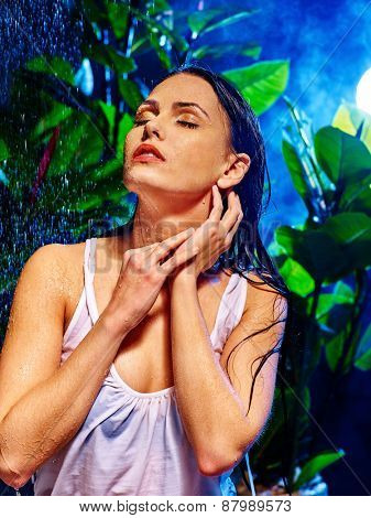 Wet woman with water drop on the background of green plants.