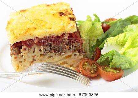 Greek pastitsio pasta topped with minced beef, tomatoes, bechamel sauce and cheese, served with a salad.
