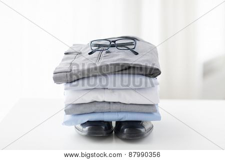 business, style, clothes, housekeeping and objects concept - close up of ironed and folded shirts and formal shoes on table at home