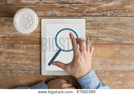 business, education, people and technology concept - close up of male hands with magnifying glass picture on tablet pc computer screen and coffee cup at table