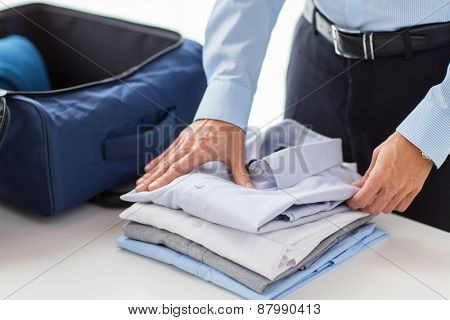 business, trip, luggage and people concept - happy businessman packing clothes into travel bag