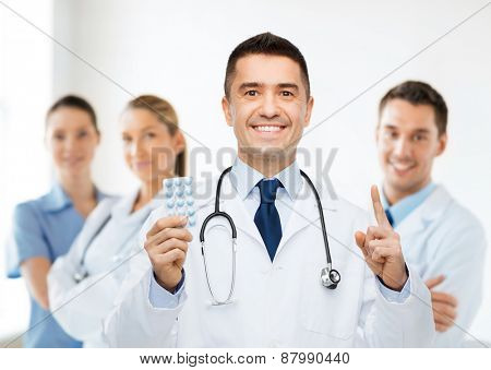 healthcare, profession, people and medicine concept - smiling male doctor in white coat with tablets pointing his finger up over group of medics at hospital background
