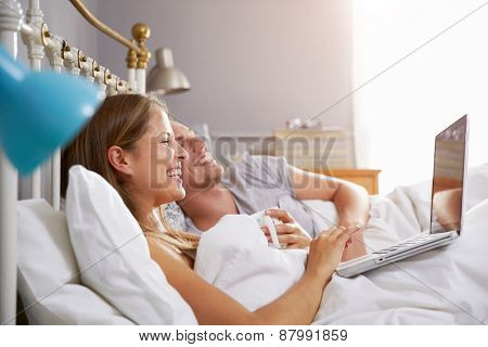 Couple Lying In Bed Looking At Laptop