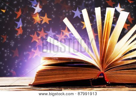 Book with light over dark background
