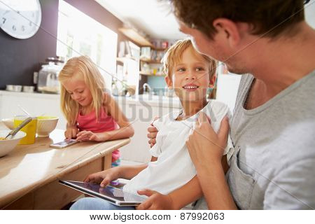 Father And Children Using Digital Devices At Breakfast Table