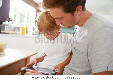 Father And Son Using Digital Tablet At Breakfast Table