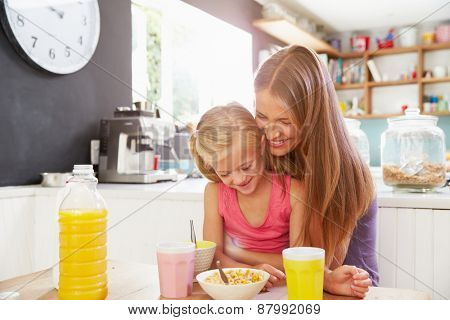 Mother And Daughter Having Breakfast At Kitchen Table
