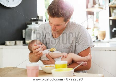 Father Holding Newborn Baby Daughter At Kitchen Table
