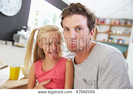 Father And Daughter Making Funny Faces At Breakfast Table