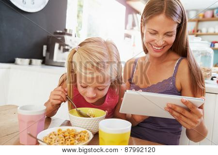 Mother And Daughter Using Digital Tablet At Breakfast Table