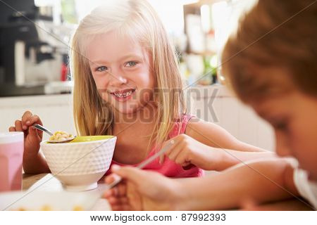 Portrait Of Children Eating Breakfast At Kitchen Table