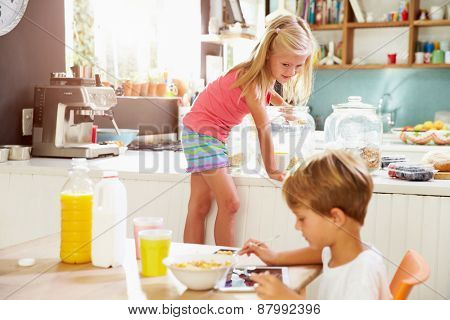 Children Eating Breakfast And Playing With Digital Tablet