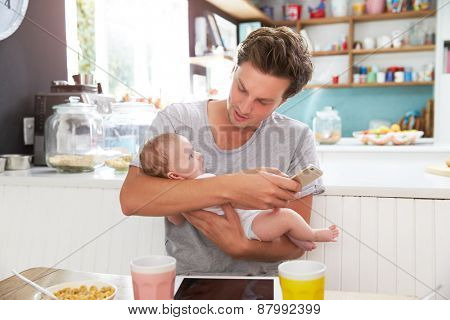 Father With Baby Daughter Checking Mobile Phone In Kitchen
