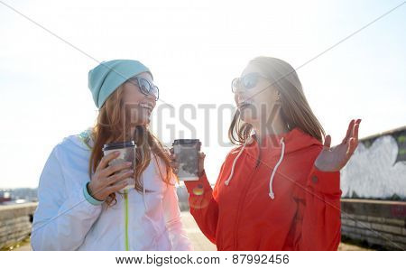 people, leisure, friendship, communication and takeaway drinks concept - happy teenage girls with coffee cups on city street