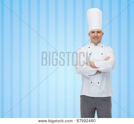 cooking, profession and people concept - happy male chef cook with crossed hands over blue striped background