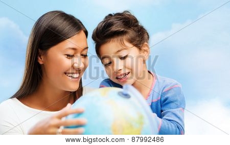 family, children, travel, geography and happy people concept - mother and daughter with globe over blue sky background