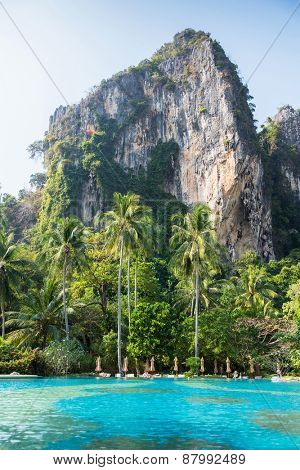 summer holidays, tourism, travel and leisure concept - swimming pool and cliff at thailand touristic resort beach