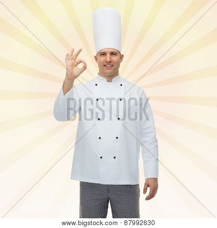 cooking, profession, gesture and people concept - happy male chef cook showing ok sign over yellow burst rays background
