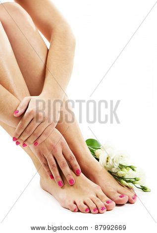 Beautiful female legs with flowers, isolated on white background