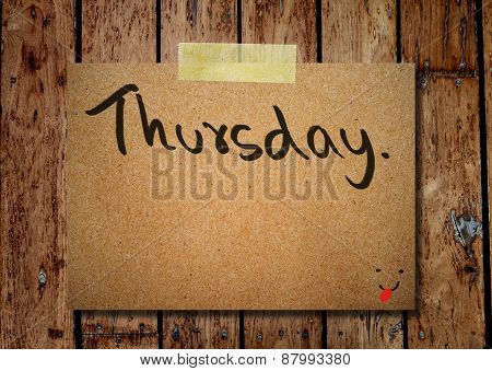 Thursday On Note Paper With Wooden Background