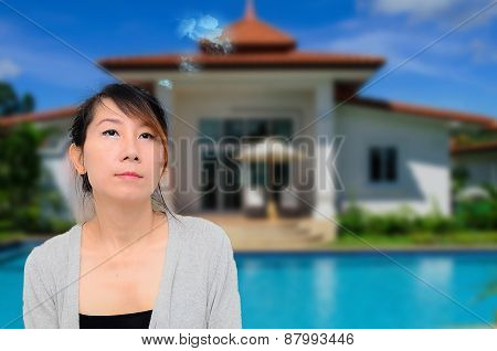 Thoughtful Smart Asian Woman In Front Of House Looking Up And To The Side.