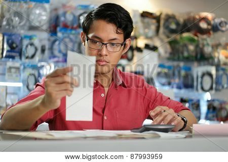 Chinese Man Working In Computer Shop Holding Bills And Invoices