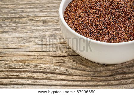 gluten free kaniwa grain (also known as baby quinoa) in a small ceramic bowl against grained wood