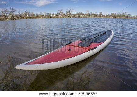 red SUP paddleboard with a paddle on a lake shore ready for paddling, spring time in Colorado