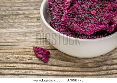 slices of dried red dragon fruit in a white, ceramic bowl against grained wood