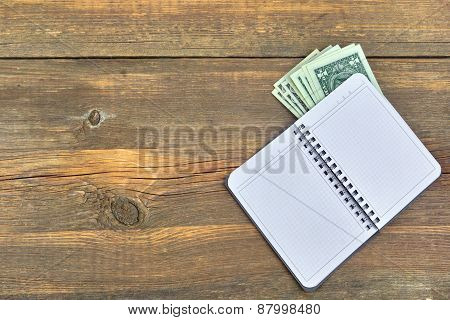 Open Notebook And Money Bills On Grunge Wood Background