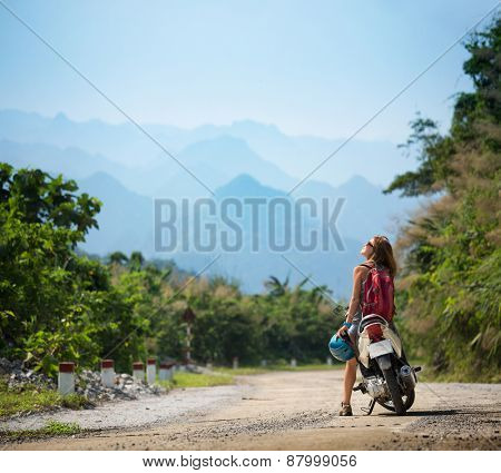 Young lady standing near motorbike and enjoying landscape view