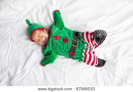 Baby in elf costume for christmas holiday on white background