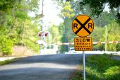pic of railroad-sign  - Railroad crossing sign on a rural road with railroad crossing in the background - JPG