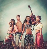 stock photo of hippy  - Multinational hippie friends with guitar in a wheat field  - JPG