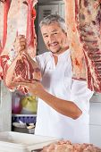 pic of slaughterhouse  - Portrait of confident male butcher holding raw meat with hook in shop - JPG