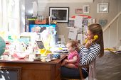 stock photo of untidiness  - Mother With Daughter Running Small Business From Home Office - JPG
