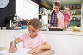 image of 11 year old  - Girl Drawing Picture As Mother Prepares Meal In Kitchen - JPG