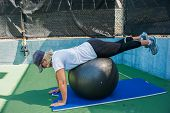 image of stability  - She strengthens her glutes on the stability ball - JPG