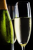 image of flute  - Champagne flutes and bottle on black background - JPG