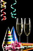 stock photo of flute  - Champagne flutes and celebration items on black background - JPG