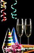 image of flute  - Champagne flutes and celebration items on black background - JPG