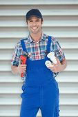 foto of pipe wrench  - Plumber holding monkey wrench and sink pipe against grey shutters - JPG