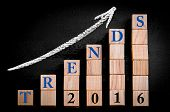 stock photo of ascending  - Message TRENDS 2016 on ascending arrow above bar graph of Wooden small cubes isolated on black background - JPG