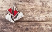 pic of wooden fence  - Two pairs of sneakers hang on a nail on a wooden fence background - JPG