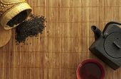 foto of black tea  - on bamboo Mat cast iron kettle and a Cup of hot tea spilled black tea - JPG