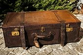 stock photo of paving stone  - Old closed locked retro vintage leather suitcase on stone paved surface closeup - JPG