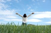 stock photo of open arms  - Woman with open arms in green field - JPG