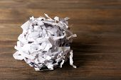 pic of strip  - Strips of destroyed paper from shredder on wooden background - JPG