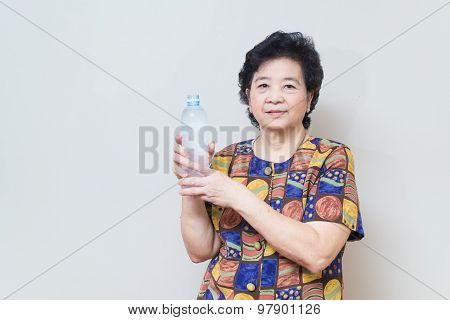 Asian Senior Woman With Bottle And Glass Of Water, On Reddish Yellow Gray Wall Background